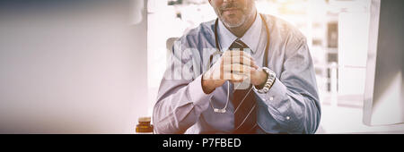 Portrait of smiling doctor with hands clasped - Stock Photo