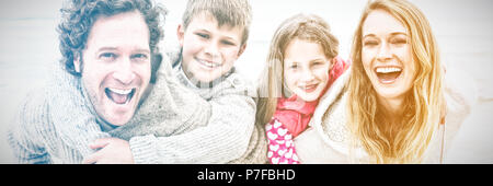 Couple piggybacking kids at the beach - Stock Photo