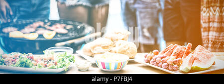Table laid with food for outdoors barbecue party - Stock Photo