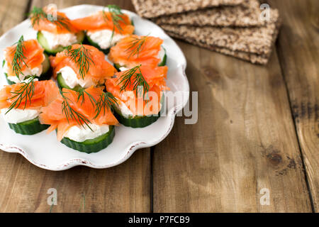 cucumber and salmon, small snacks on a plate. Copy space - Stock Photo