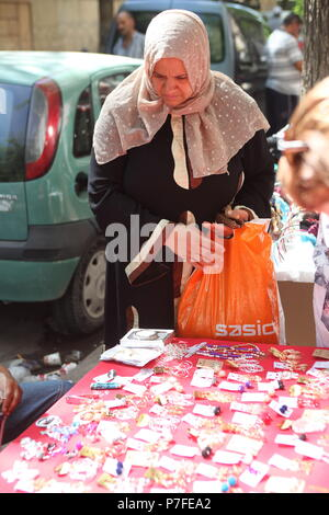 On the street in Tunis, the capital of Tunisia middle age muslim lady buys some bijouterie on the street market in down town - Stock Photo