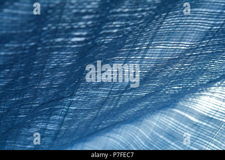 Monochrome plaid pattern of tarps in sunlight and wind creating a canopy and shade from the sun - Stock Photo