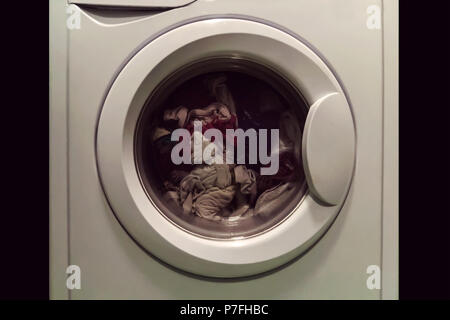 A close up of a washing machine loaded with clothes isolated on white background. The Laundry in the washing machine with the closed open. - Stock Photo