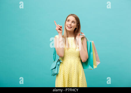 Beautiful young girl in yellow dress points to something with her finger - Stock Photo