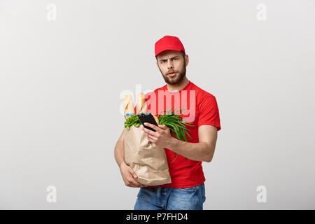 Delivery man holding paper bag with food and shock or angry with something in mobile phone on white background - Stock Photo
