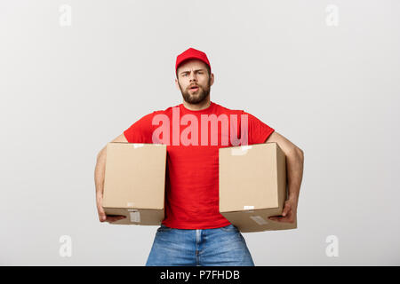 Exhausted handsome delivery man holding boxes and taking a break. Isolated on white - Stock Photo