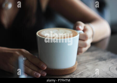 Large white Cup with cappuccino in female hands, selective focus - Stock Photo