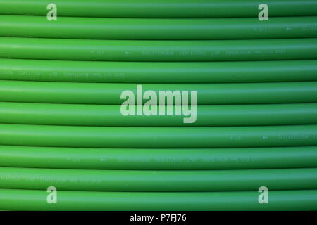 Green outer shell of thick optical cable forming bars pattern. - Stock Photo