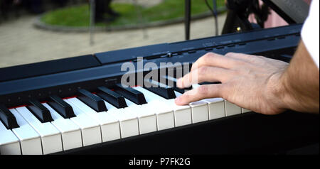 young musician playing synthesizer in an outdoor performance,image of a - Stock Photo
