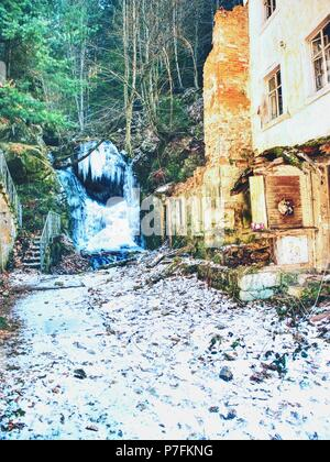 Frozen waterfall between rocks. Fallen icicle bellow waterfall, stony and mossy stream bank. - Stock Photo