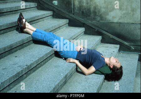 Woman sleeping with head down on stairs, Berlin, Germany - Stock Photo