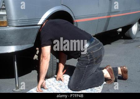 Man repairs car, Berlin, Germany - Stock Photo