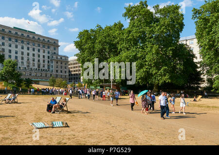 Tourists arriving from Green Park Underground station, walking through a scorched Green Park, London UK, during the July 2018 heatwave - Stock Photo