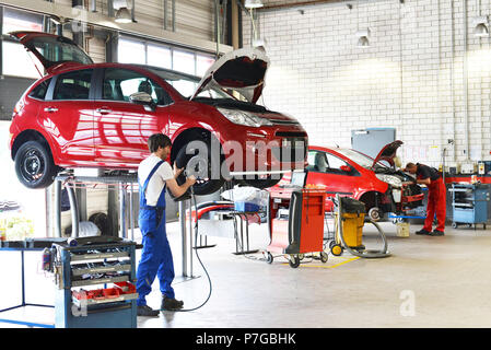 tyre change on the car by mechanics in a workshop - Stock Photo