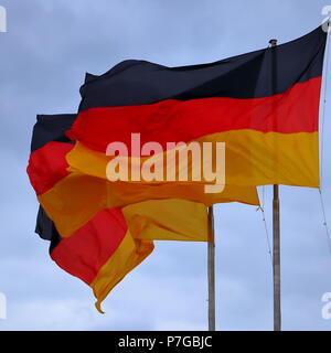 Three flags of Germany, German flag blowing in the wind. - Stock Photo