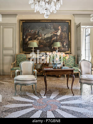 Gingham chairs with side table and artwork in mosaic tiled interior of 18th century chateaux, St Remy de Provence - Stock Photo