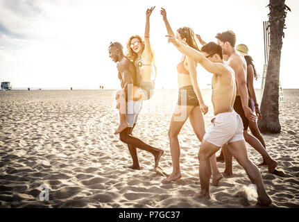 Group of friends making big party and games on the beach - Stock Photo