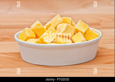 Cut of mango cut to cubes isolated on a plate on wooden background - Stock Photo