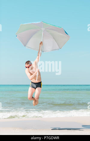 Young attractive fit man, male, happy, smiling, jumping mid-air, in air on beach on sunny day with red sunglasses in Florida panhandle with ocean, hol - Stock Photo
