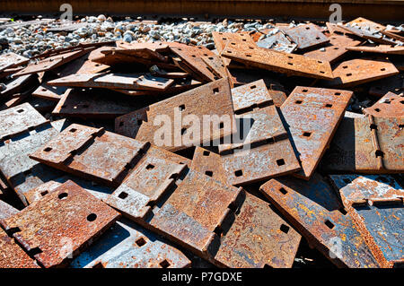 Pile of scrap rail railway railroad track rusty grungy metal plates covered in rust, abandoned in junk yard with grunge - Stock Photo