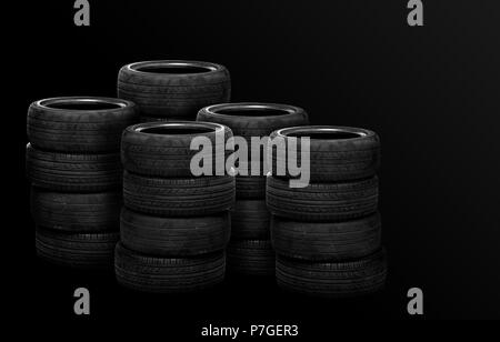 Old tires stacked, isolated on black background - Stock Photo
