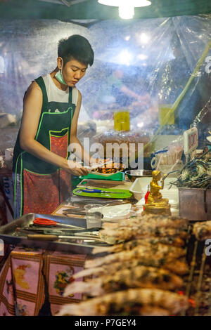CHIANG MAI, THAILAND - AUGUST 27: Food vendor prepares seafood at the Saturday Night Market (Walking Street) for sale on August 27, 2016 in Chiang Mai - Stock Photo