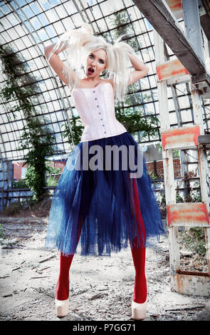Portrait of the cute strange freak girl. Attractive weird woman wearing motley corset, tights and tutu skirt in ruined place. Odd fashion - Stock Photo