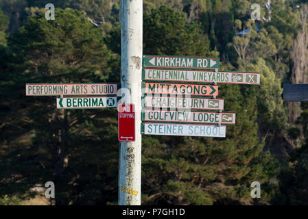 Nine different signs on the one signpost in Bowral, NSW, Australia - Stock Photo