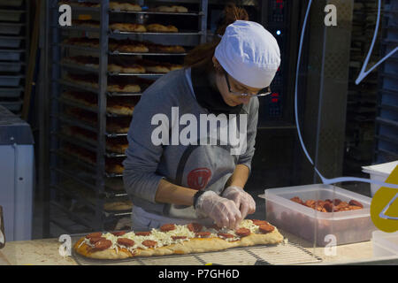 FLORENCE, ITALY - NOVEMBER 22 2015: Girl preparing a pizza inside the central market in Florence, Italy - Stock Photo