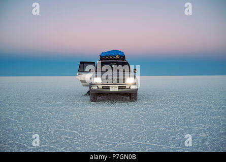Land Cruiser during twilight in Uyuni salt flats (Salar de Uyuni) Bolivia, South America. Jun 2018 - Stock Photo