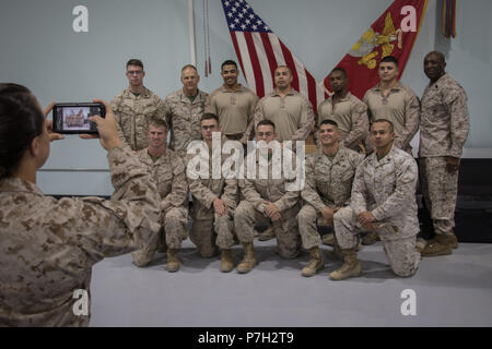 UNDISCLOSED LOCATION, MIDDLE EAST – The Commandant of the Marine Corps Gen. Robert B. Neller (second from far left) and Sergeant Major of the Marine Corps Ronald L. Green (far right), pose for a group photo with Marines from Special Purpose Marine Air-Ground Task Force, Crisis Response-Central Command (SPMAGTF-CR-CC) June 26, 2018. Neller spoke to SPMAGTF-CR-CC as a whole and praised Marines for their unit's performance thus far, encouraging them to stay on the right path. (U.S. Marine Corps photo by Sgt. Royce Dorman) - Stock Photo