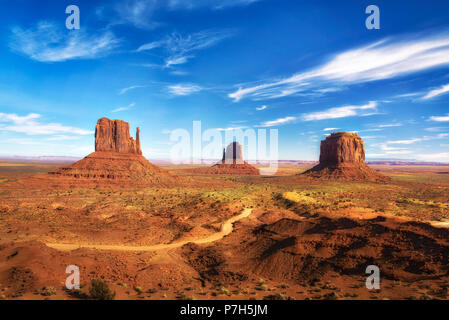 Dirt road leading through Monument Valley on the border between Arizona and Utah, USA. - Stock Photo
