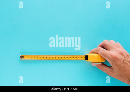 Handyman measuring size with tape meter, hand with tool isolated on blue background - Stock Photo