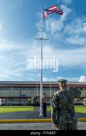180701-N-WR252-034 SANTA RITA, Guam (July 1, 2018) Lt. j.g. Elisabeth Staab salutes the American flag during morning colors at 30th Naval Construction Regiment (NCR) headquarters, officially marking its relocation to Guam from Port Hueneme, California. This move streamlines operational effectiveness and establishes the regiment as a forward-deployed operational staff capable of commanding and controlling Naval Construction Force units deployed to the 7th Fleet area of operations. (U.S. Navy Photo by Chief Mass Communication Specialist Matthew R. White/ released) - Stock Photo
