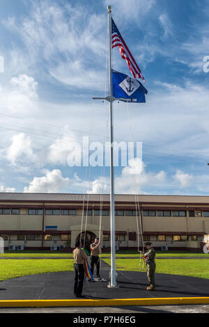 180701-N-WR252-041 SANTA RITA, Guam (July 1, 2018) Sailors hoist the 30th Naval Construction Regiment (NCR) command flag above its new headquarters officially marking its relocation to Guam from Port Hueneme, California. This move streamlines operational effectiveness and establishes the regiment as a forward-deployed operational staff capable of commanding and controlling Naval Construction Force units deployed to the 7th Fleet area of operations. (U.S. Navy Photo by Chief Mass Communication Specialist Matthew R. White/ released) - Stock Photo