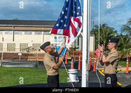 180701-N-WR252-027 SANTA RITA, Guam (July 1, 2018) Yeoman 1st Class Travis Aquino, left, and Equipment Operator 1st Class Clinton Burch raise the American flag over the 30th Naval Construction Regiment (NCR) headquarters, officially marking its relocation to Guam from Port Hueneme, California. This move streamlines operational effectiveness and establishes the regiment as a forward-deployed operational staff capable of commanding and controlling Naval Construction Force units deployed to the 7th Fleet area of operations.  (U.S. Navy Photo by Chief Mass Communication Specialist Matthew R. White - Stock Photo