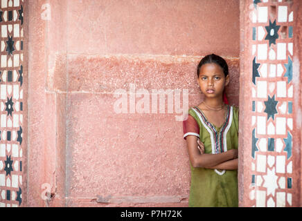 Beautiful young Indian girl in traditional green dress leaning against temple wall Agra Uttar Pradesh - Stock Photo