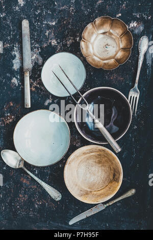 Flat lay with crockery and cuttlery of different materials on a rusty dark background. Food styling concept - Stock Photo