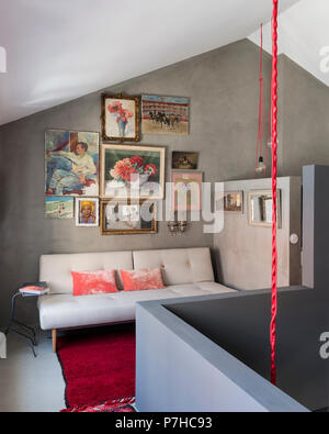 Colourful mix of still lifes and portraits on wall of seating area in modern loft style apartment - Stock Photo