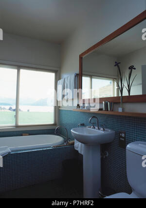 Mirror Above Wash Basin In White Vanity Unit Beside Glass