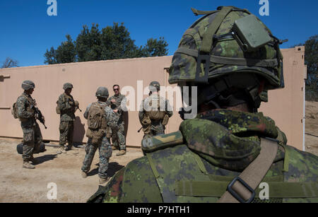 180702-M-PG096-1075 MARINE CORPS BASE CAMP PENDLETON, Calif. (July 2, 2018) – Canadian Army Sdt. Michael Simard, a rifleman with Royal 22e Régiment, observes the U.S. Marines with 2nd Battalion, 1st Marine Regiment, during a combat-town drill as part of Rim of the Pacific (RIMPAC) exercise at Marine Corps Base Camp Pendleton, California, July 2, 2018. RIMPAC demonstrates the value of amphibious forces and provides high-value training for task-organized, highly-capable Marine Air-Ground Task Forces enhancing the critical crisis response capability of U.S. Marines in the Pacific. Twenty-five nat - Stock Photo