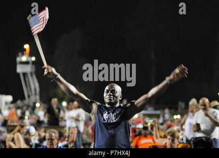 """FORT LEE, Va. (July 5, 2018) -- Sgt. Bamidele Agbaje waves the American flag from side to side while a rendition of Lee Greenwood's """"God Bless the USA"""" was performed during Fort Lee's Fourth at the Fort celebration at Williams Stadium July 4. The annual event attracted thousands who gathered for fireworks, vendor-served food and refreshments, family attractions and music from the group Trademark and Fort Lee's 392nd Army Band. Agbaje, a native of Nigeria, is an Advanced Leader Course student attending the Logistics Noncommissioned Officer Academy. - Stock Photo"""