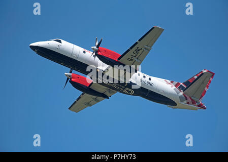 Loganair Saab 340 G-LGNC taking off from Inverness Airport on it's daily flight to Stornoway in the Outer Hebrides. - Stock Photo