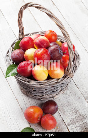 Fresh ripe peaches and plums in basket on wooden table - Stock Photo