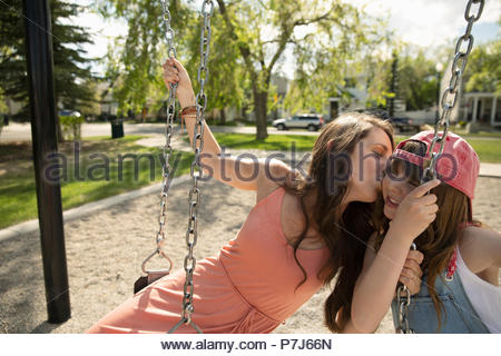 Affectionate mother kissing daughter on swing at sunny playground - Stock Photo