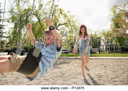 Sister pushing brother on swing at sunny playground - Stock Photo