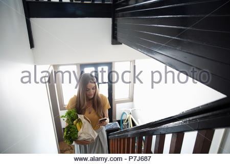 Young woman with smart phone and groceries climbing apartment stairs - Stock Photo