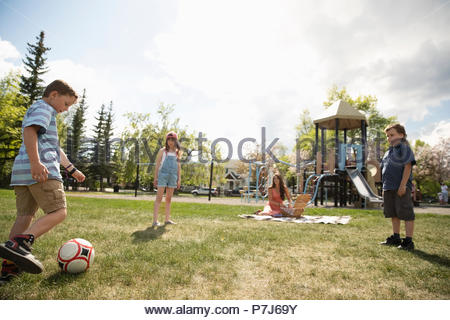 Mother on picnic blanket watching kids playing soccer in sunny park - Stock Photo