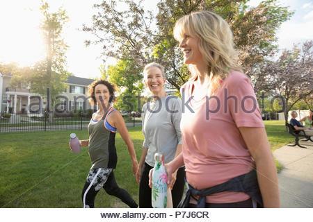 Smiling senior women walking, exercising in sunny park - Stock Photo
