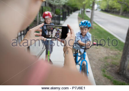 Mother with camera phone photographing sons riding bicycle and scooter on neighborhood sidewalk - Stock Photo
